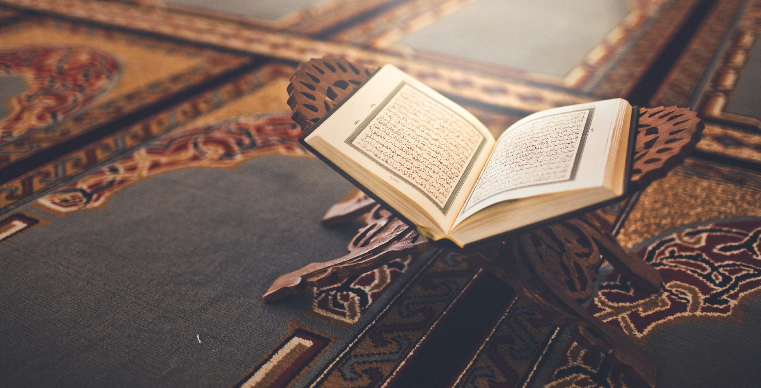 Quran open on stand near mosque floor